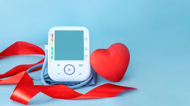 Ciśnieniomierz czerwona jedwabna wstążka i czerwona figura serca na niebieskim tle