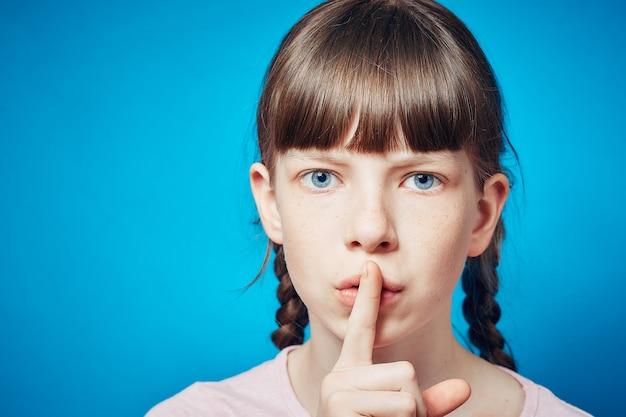 Cisza i spokój. mała dziewczynka shushing widza. palec na ustach. wyraz twarzy