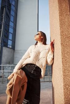 Cisza i spokój. młoda piękna dziewczyna w ciepłych ubraniach spaceruje po mieście w weekendy
