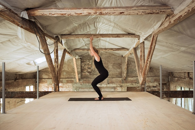 Cisza. młoda kobieta lekkoatletycznego ćwiczy jogę na opuszczonym budynku. równowaga zdrowia psychicznego i fizycznego. pojęcie zdrowego stylu życia, sportu, aktywności, utraty wagi, koncentracji.