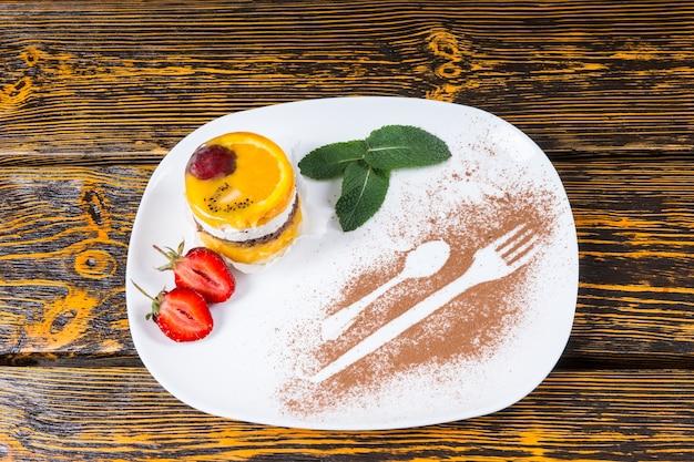 Citrus z musem cytrusowym zwieńczony kolorowym plasterkiem pomarańczy i jagód podawany ze świeżymi liśćmi truskawek i mięty na talerzu ozdobionym proszkiem kakaowym sylwetki naczyń, widok pod dużym kątem