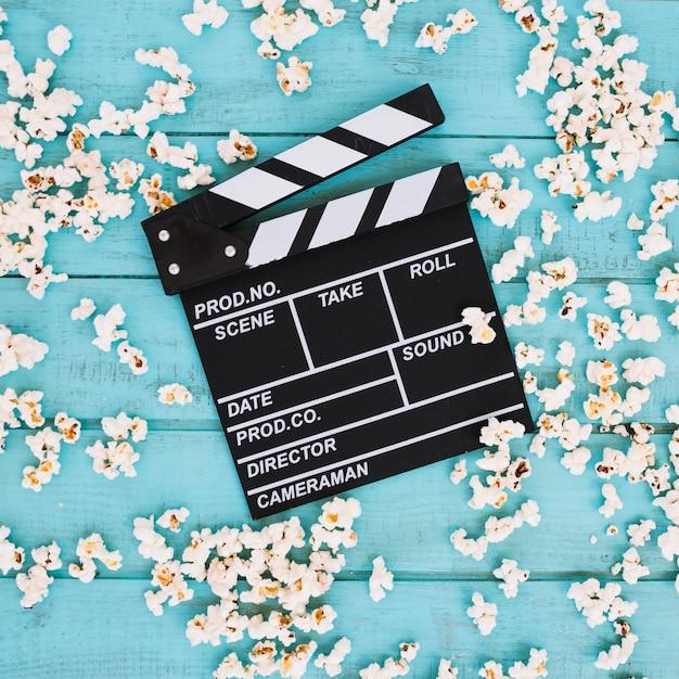 Clapperboard na stercie rozlany popcorn