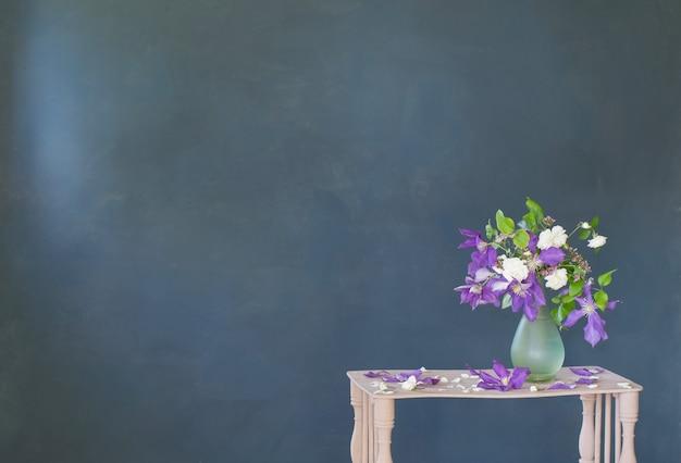 Clematis kwiaty w szklanym wazonie na vintage drewnianej półce