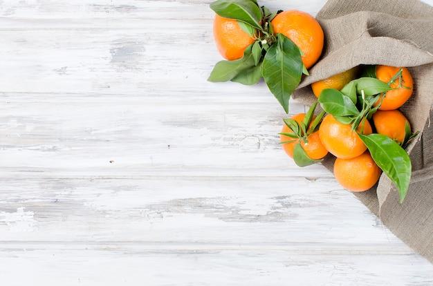 Clementine mandarynki z liśćmi na drewnianym stole.