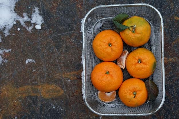 Clementines mandarynki jako boże narodzenie wystrój na tle śniegu.