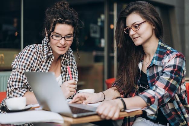 Clever studentów. dwie dziewczynki pracują z laptopem