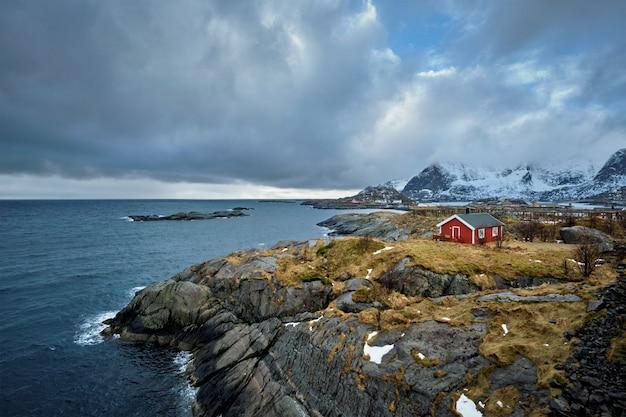 Clif z tradycyjnym czerwonym rorbu domem na lofoten islands, norwegia