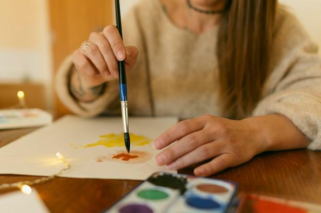 Close-up artysta za pomocą pędzla na papierze