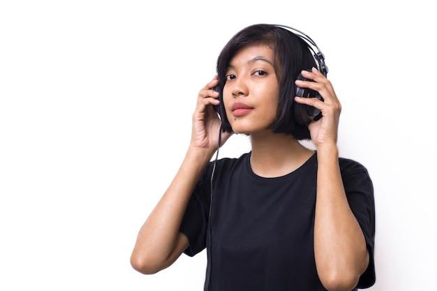 Close-up asian kobieta ze słuchawkami, ciesząc się muzyką i kopiowaniem przestrzeni