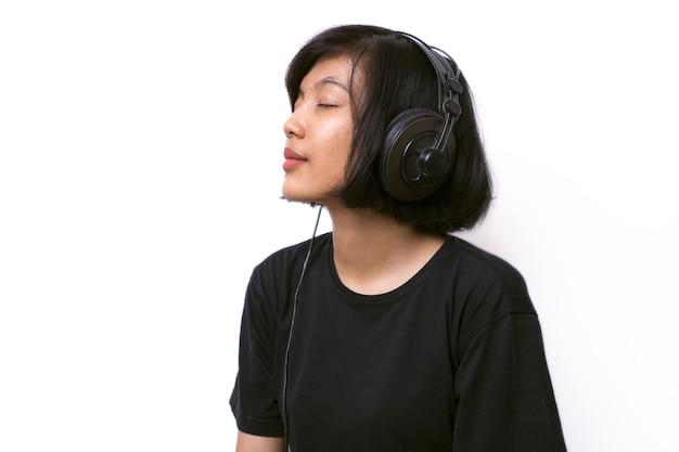 Close-up asian kobieta ze słuchawkami, ciesząc się muzyką na białej przestrzeni