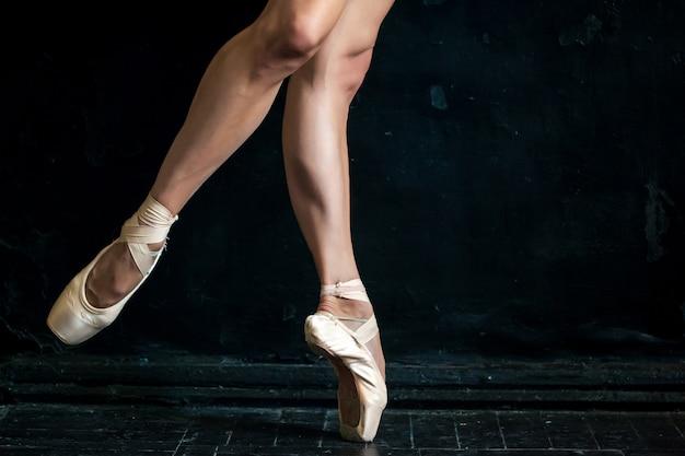 Close-up baleriny nogi i pointes na czarnej drewnianej podłodze