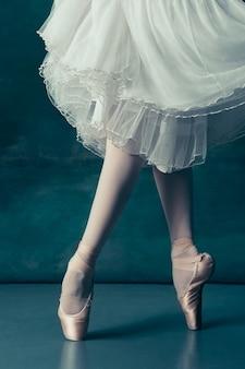 Close-up baleriny nogi w pointes na szarej drewnianej podłodze