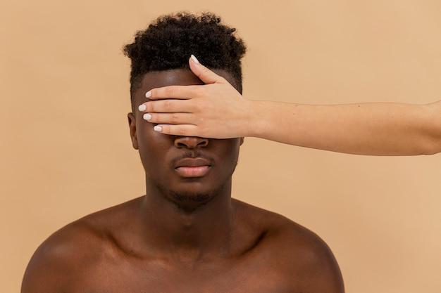 Close-up biała ręka obejmująca oczy czarnego człowieka