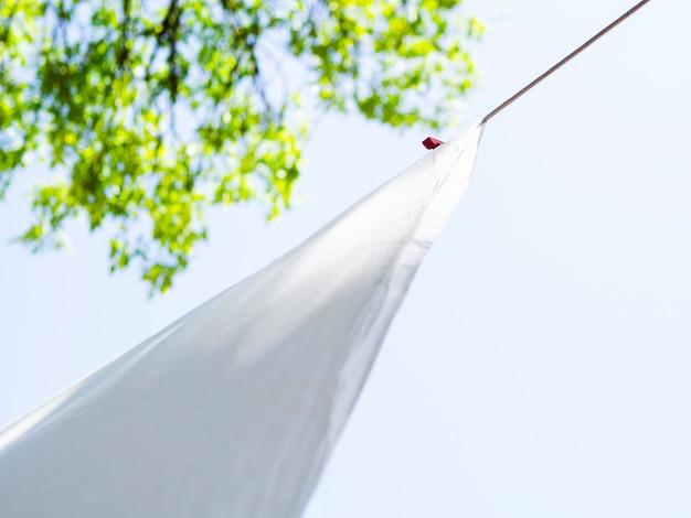 Close-up białe prześcieradło suszenia na linii