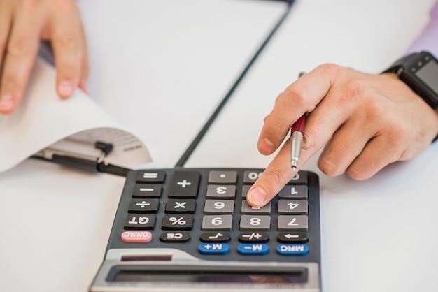 Close-up biznesmen obliczania faktur przy użyciu kalkulatora