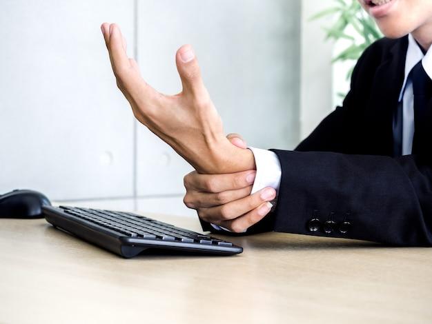 Close-up biznesmen w garniturze coraz ból dłoni podczas korzystania z komputera przenośnego w biurze