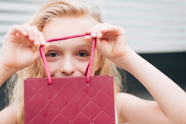 Close-up blondynki dziewczyny mienia prezenta torba
