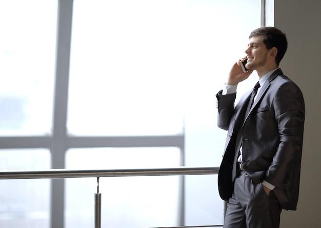 Close up.businessman rozmawia na smartfonie, stojąc w pobliżu okna biura.