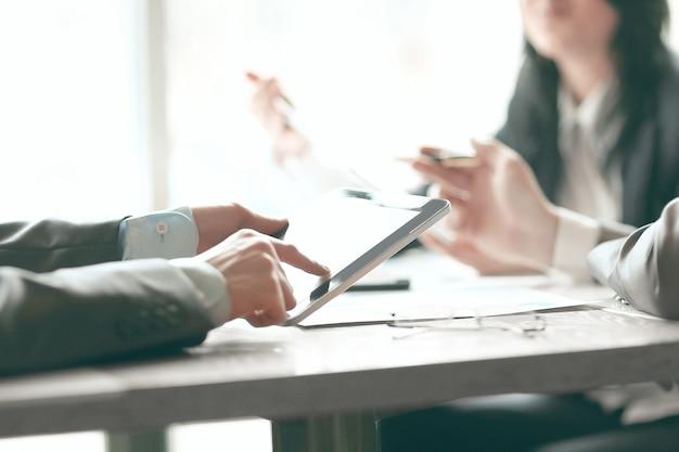 Close up.businessman używa cyfrowego tabletu do sprawdzania danych finansowych