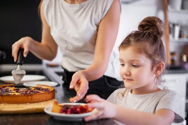 Close-up córka i matka udostępnianie ciasto razem