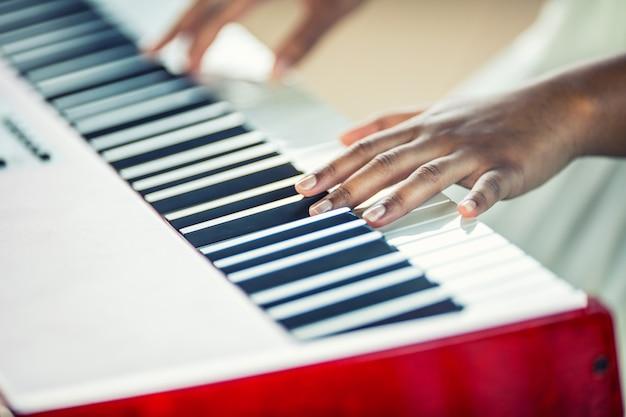 Close-up czarna kobieta ręce grając na pianinie.