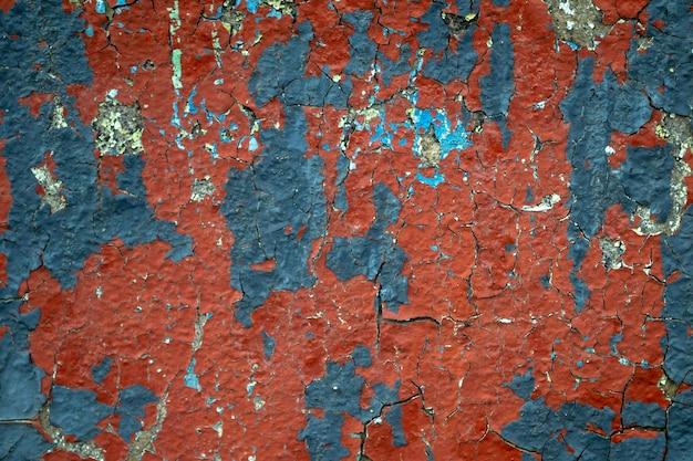 Close-up czerwoną i niebieską farbą na starej betonowej ścianie. zwietrzała ściana z odpryskami farby. pęknięta tekstura, streszczenie tło.