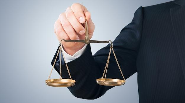 Close-up człowiek biznesu trzymający wagę w ręku na niewyraźnym szarym tle
