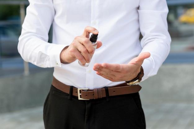 Close-up człowiek za pomocą środka dezynfekującego do rąk