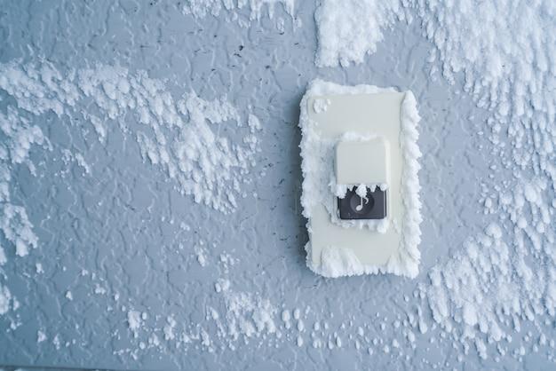 Close-up doorbell przycisk pokrywa z białym śniegu.