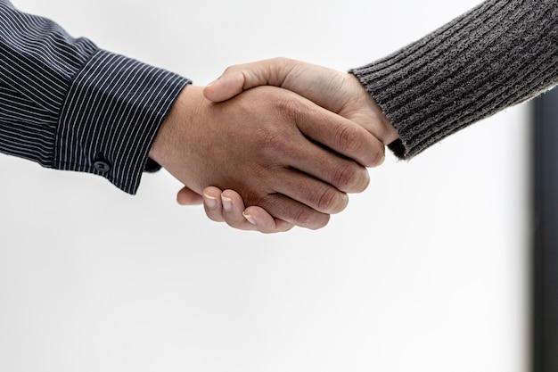 Close-up dwóch biznesmenów trzymających się za ręce, dwóch biznesmenów uzgadniają wspólnie interesy i uścisk dłoni po udanych negocjacjach. uścisk dłoni to zachodnie powitanie lub gratulacje.