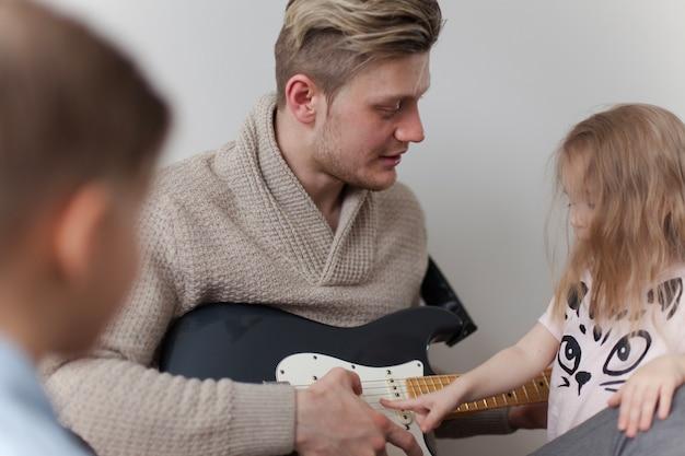 Close-up dziewczyna dotykania gitarę ojca