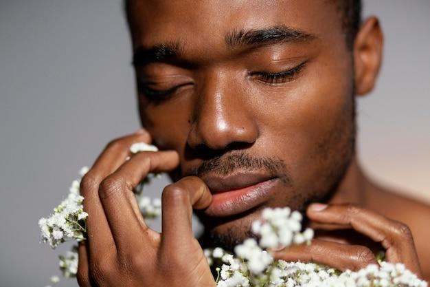Close-up ekspresyjny mężczyzna wąchający kwiaty