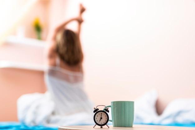 Close-up filiżanka i zegar z rozciągającą kobietą w tle