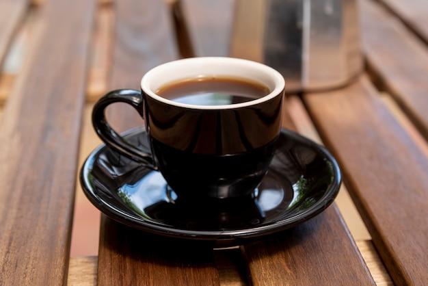 Close-up filiżanka kawy z drewnianym tłem