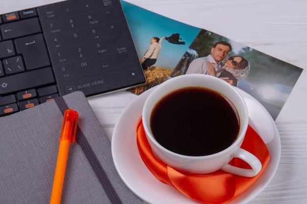 Close-up filiżanka kawy z klawiaturą komputera i piórem.
