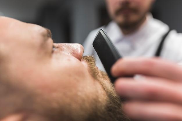 Close-up fryzjer czesanie wąsy klienta