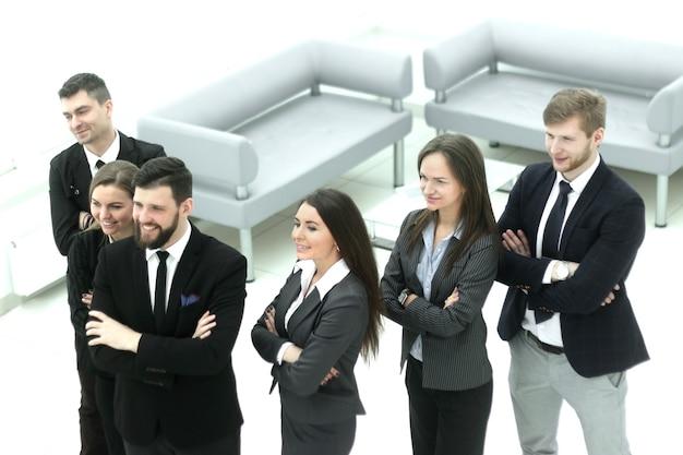 Close up.grupa odnoszących sukcesy ludzi biznesu stojących w holu biurowym