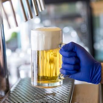 Close-up kelner z rękawiczkami i kuflem piwa