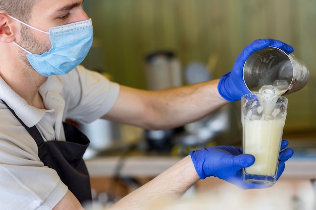 Close-up kelner z rękawiczkami i maską w pracy