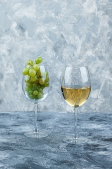 Close-up kieliszek białych winogron ze szklanką whisky na ciemnym i jasnoniebieskim tle marmuru. pionowy