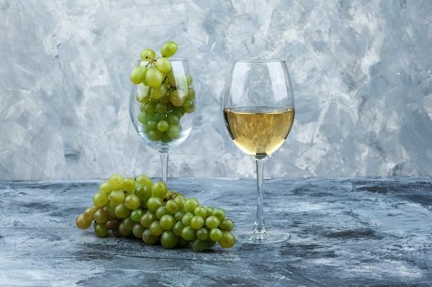 Close-up kieliszek białych winogron ze szklanką whisky na ciemnym i jasnoniebieskim tle marmuru. poziomy