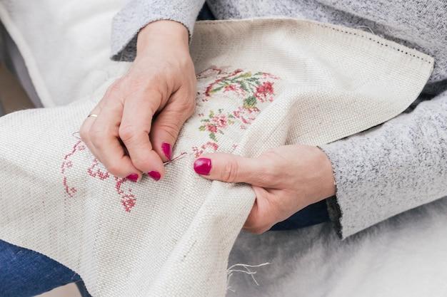 Close-up kobiecej ręki cross stitching