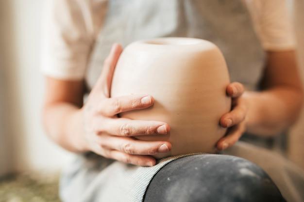 Close-up kobiet garncarza gospodarstwa gliniany garnek na jej kolanach