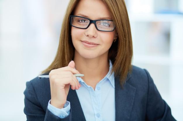Close-up kobiet wykonawczej w okularach trzyma pióro