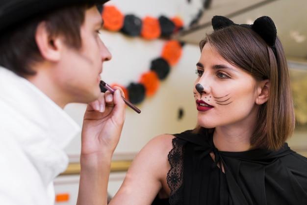 Close-up kobieta malowanie twarzy mężczyzny
