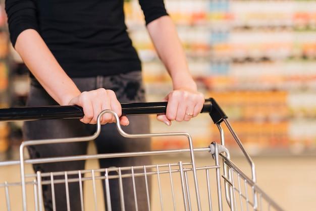 Close-up kobieta pcha wózek na zakupy