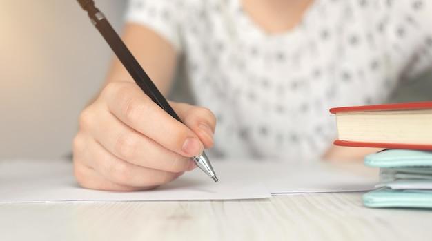 Close-up kobieta pisze, drewniany stół. koncepcja edukacji, nauki i podpisywania dokumentów. zdjęcie w tle papierkowej roboty