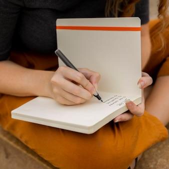 Close-up kobieta pisze w dzienniku