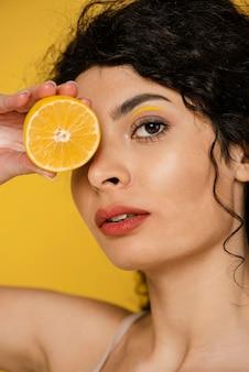 Close-up kobieta pozuje z plasterkiem cytryny