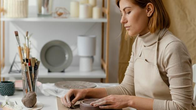 Close-up kobieta robi ceramice w domu